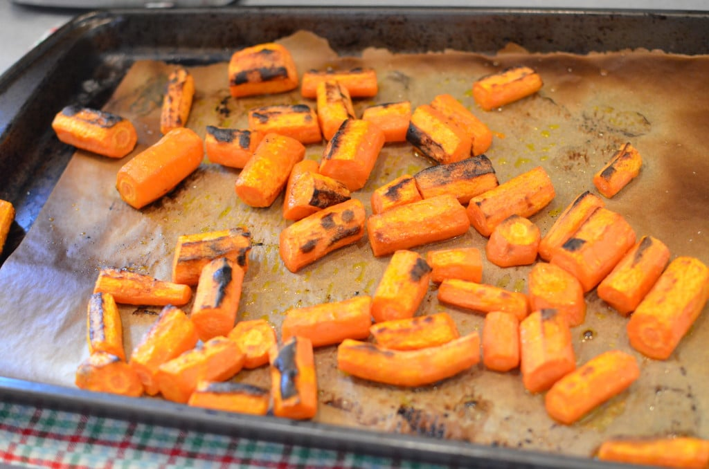 Baked cut up carrot chunks on baking sheet.