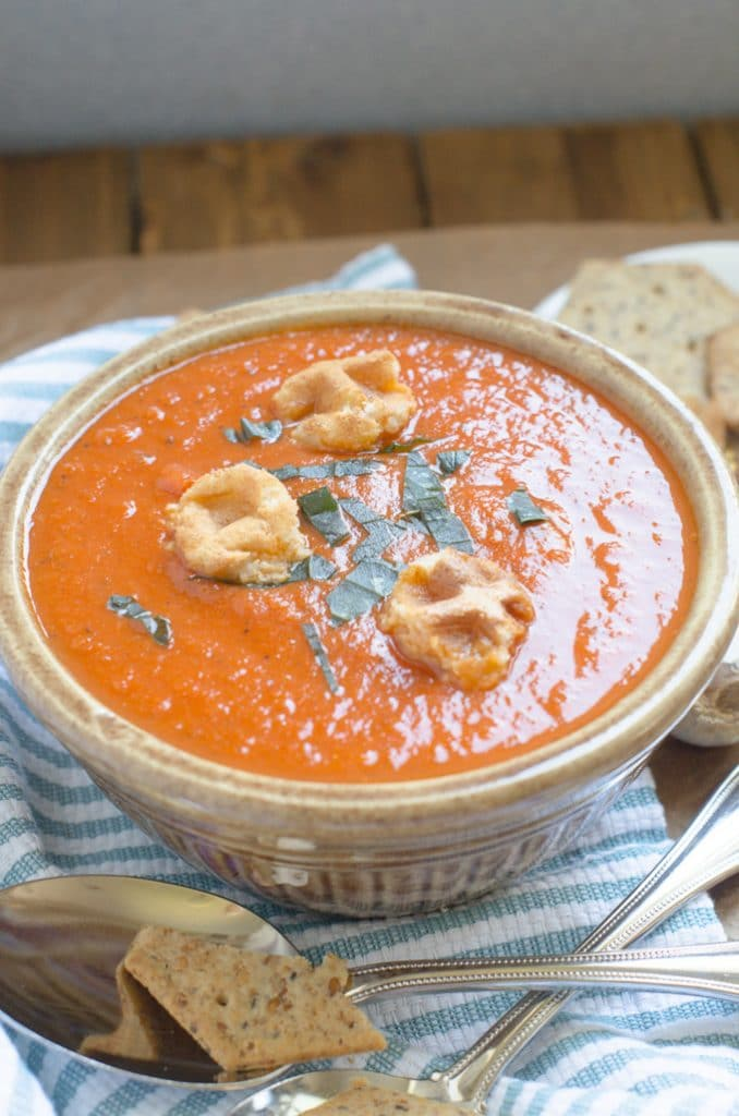 vegan tomato soup in bowl with chopped basil and croutons