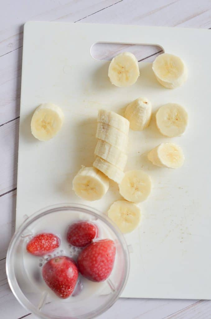 Smoothie ingredients in blender container and sliced bananas on counter.
