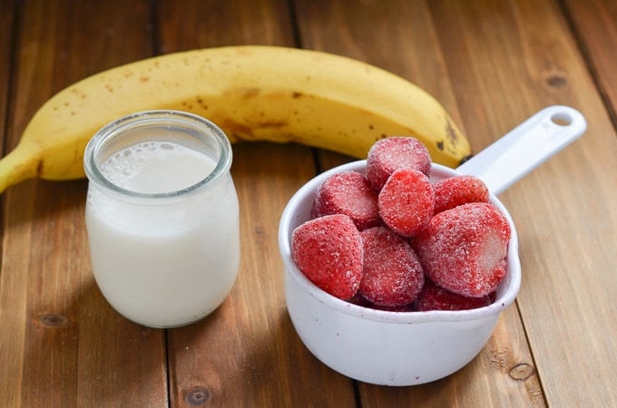 ingredients for strawberry banana smoothie on counter.
