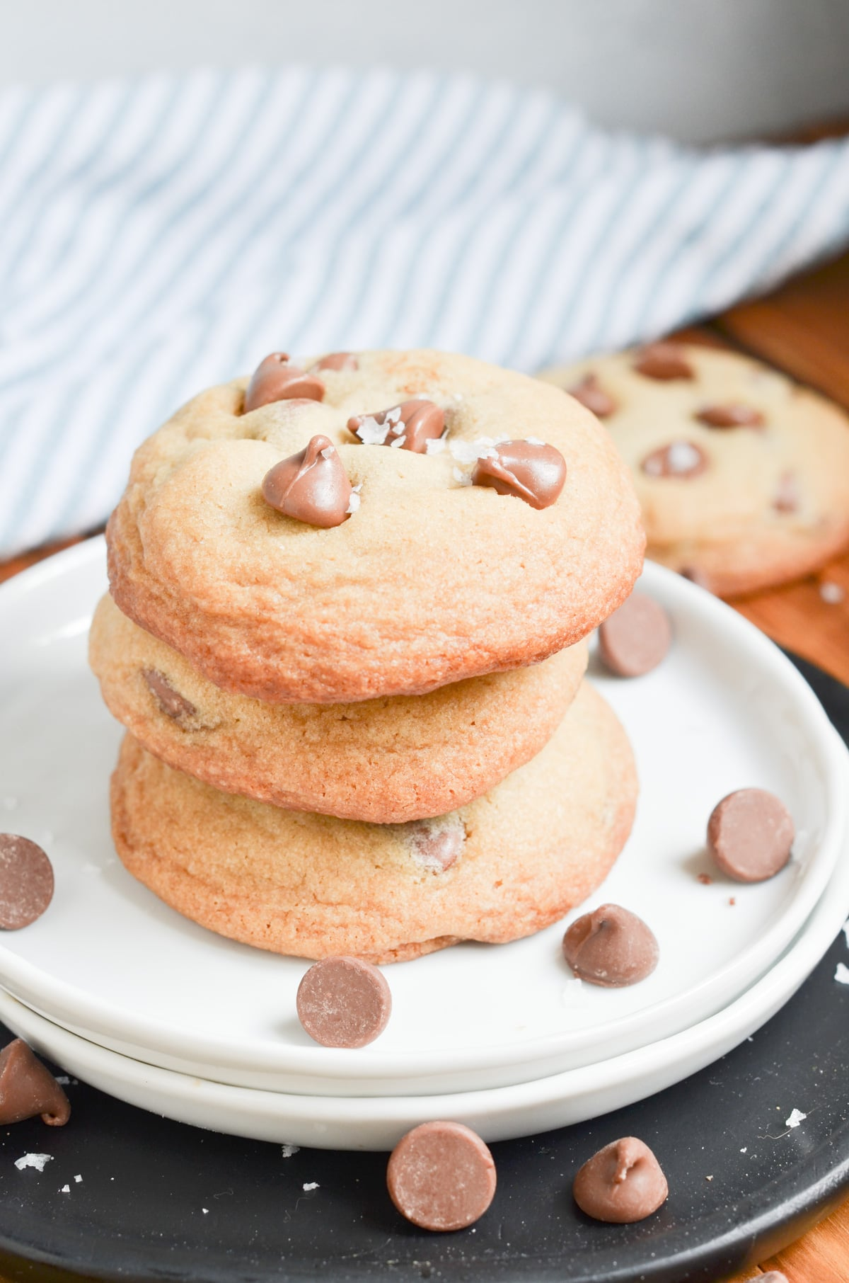 chocolate chip cookies stacked on a white plate.