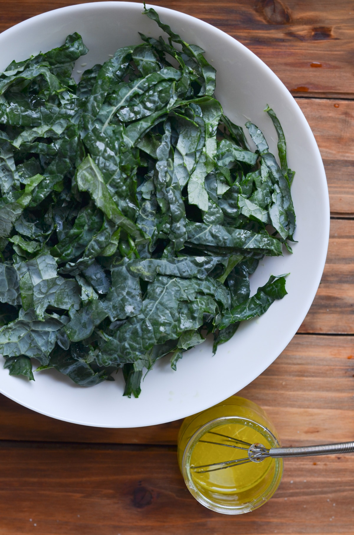 kale in white salad bowl with lemon dressing on the side.