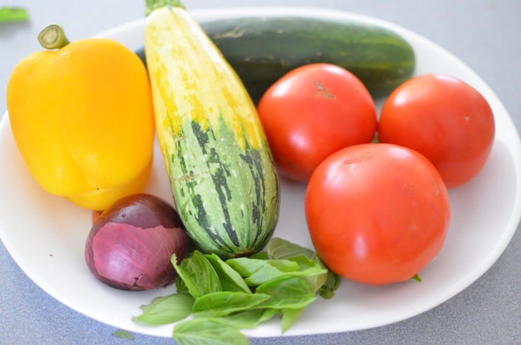 Farm Fresh Ingredients on a plate (yellow pepper, tomatoes, cucumber, squash and basil leaves)