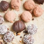 chocolate truffles with various toppings on a parchment lined baking sheet.