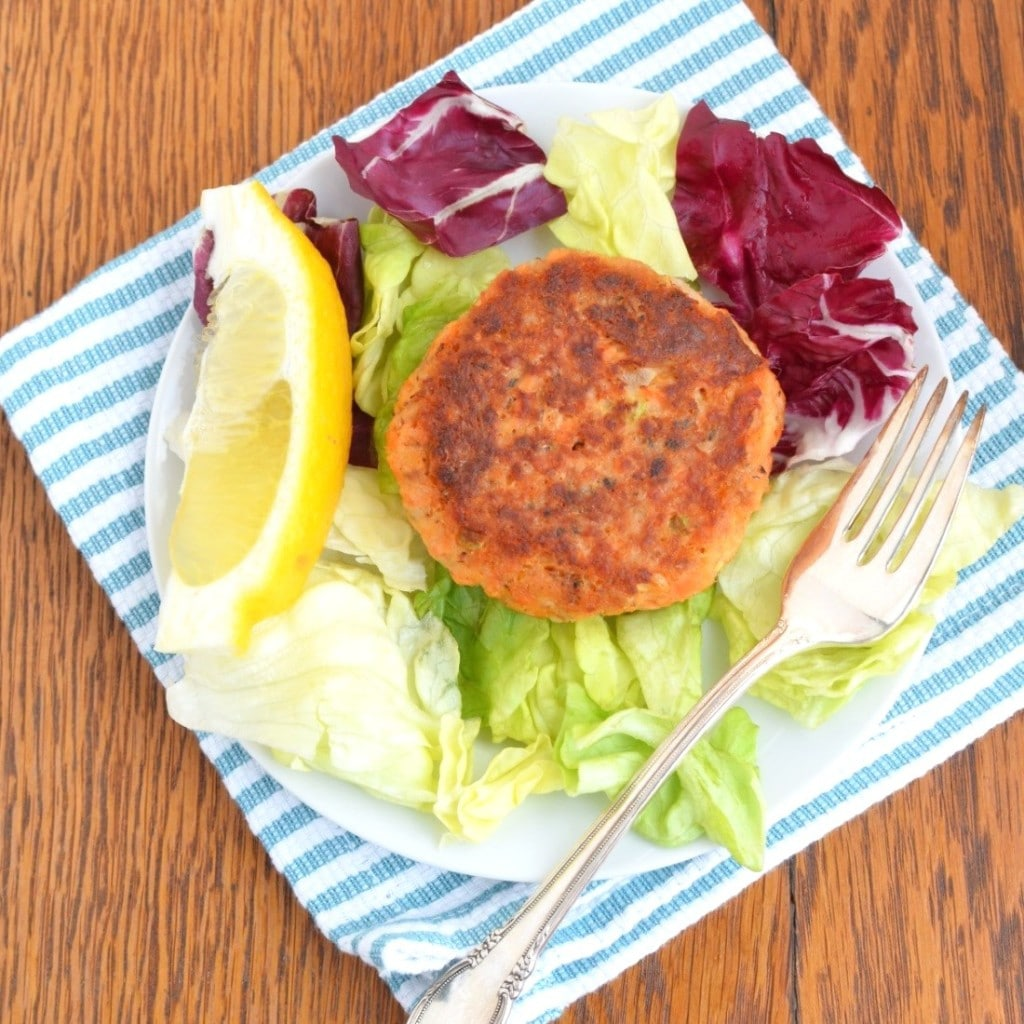 Paleo Salmon Cake on plate with lemon wedge, lettuce and fork - 24 Carrot Kitchen