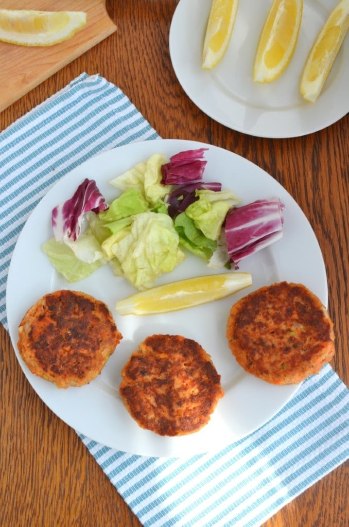 Paleo Salmon Cakes on plate with lettuce and a lemon wedge - 24 Carrot Kitchen