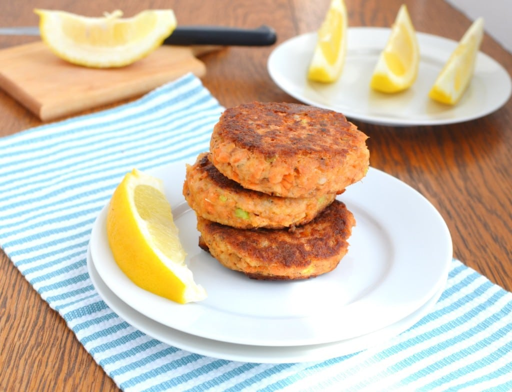 Paleo Salmon Cakes on plate with a lemon wedge - 24 Carrot Kitchen