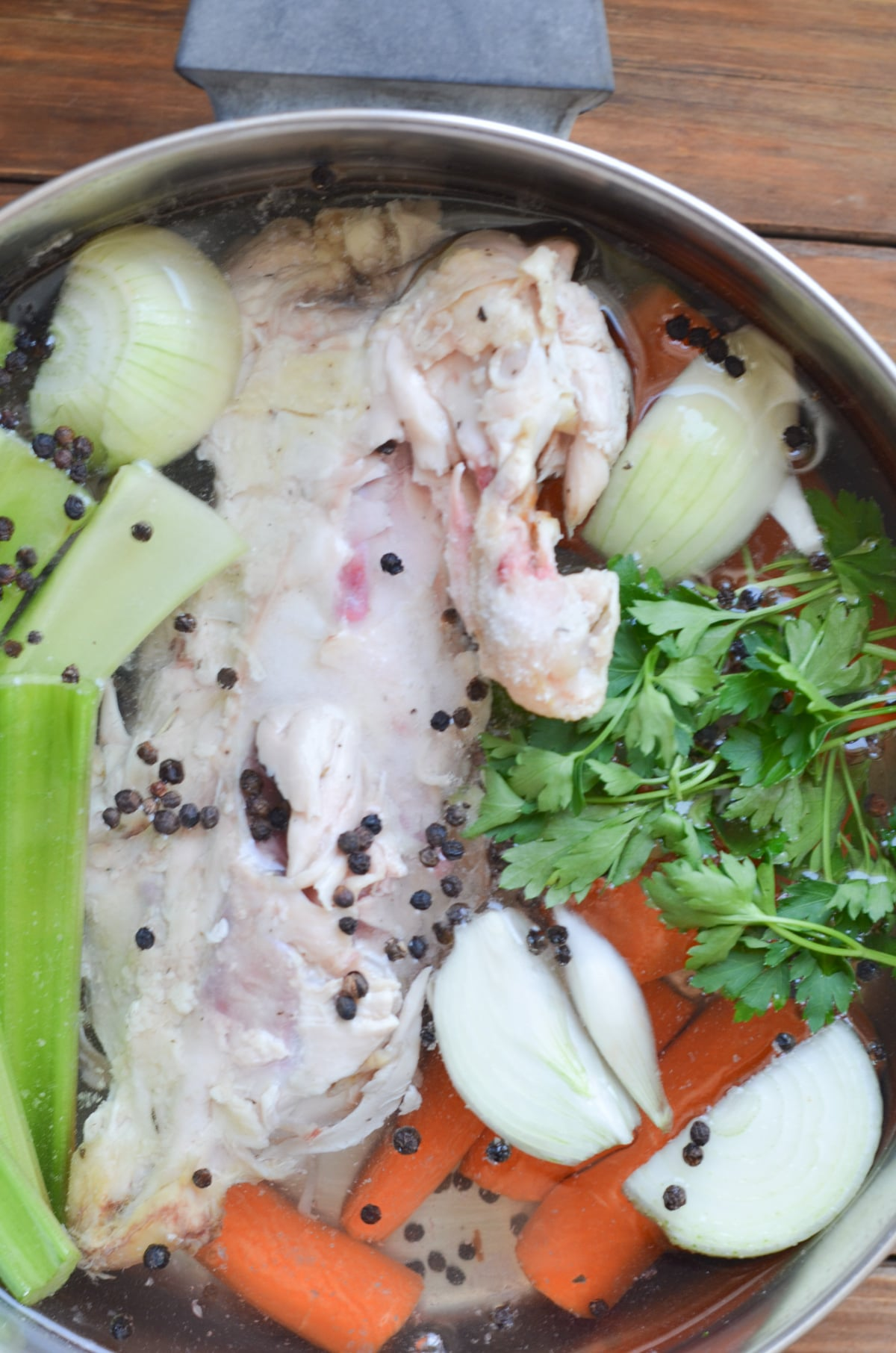 chicken bones, vegetables, herbs, spices and water in soup pot.