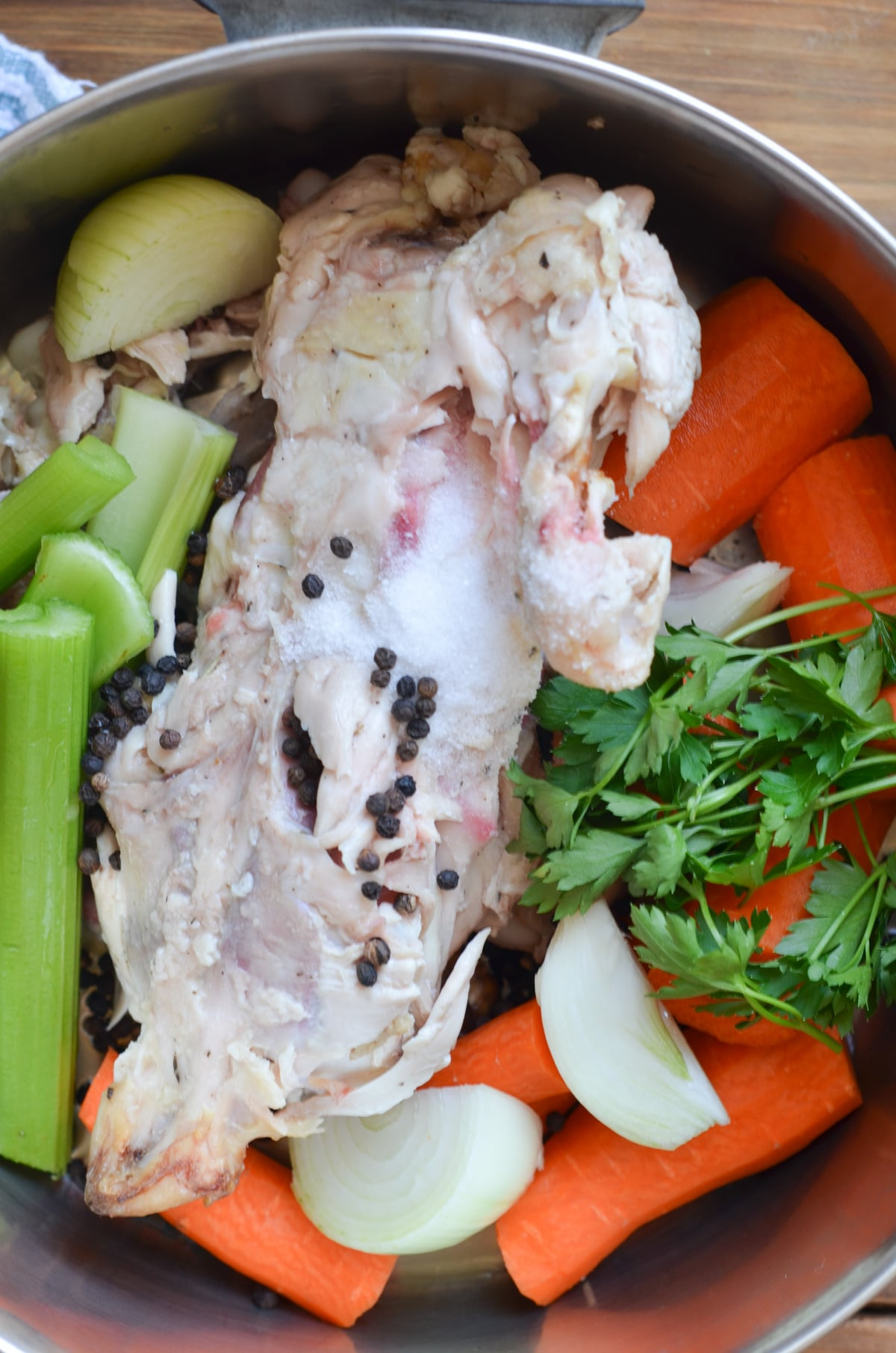 vegetables, chicken bones, herbs, spices in bottom of soup pot.