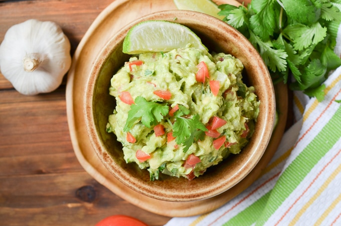 guacamole in a bowl with wedge of lime, and cilantro.