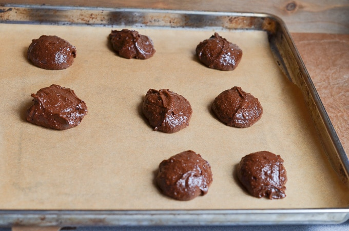 Chocolate Fudge cookies on baking pan lined with parchment ready to bake.