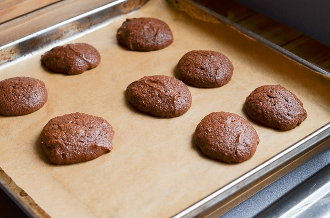 Chocolate fudge cookies baked on parchment lined baking pan.