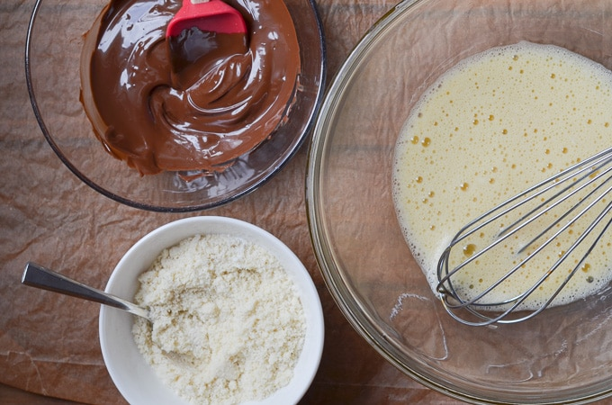 eggs whisked in mixing bowl, bowl of dry ingredients, bowl of melted chocolate on counter.