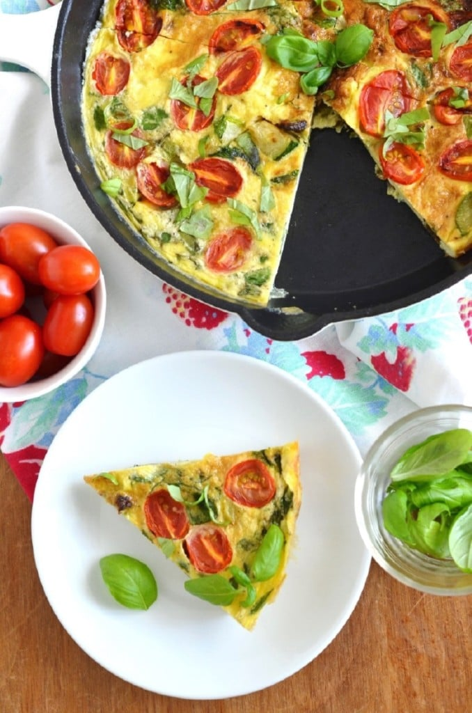 Paleo Fritatta in pan, slice on plate, bowl of tomatoes on table. - 24 Carrot Kitchen