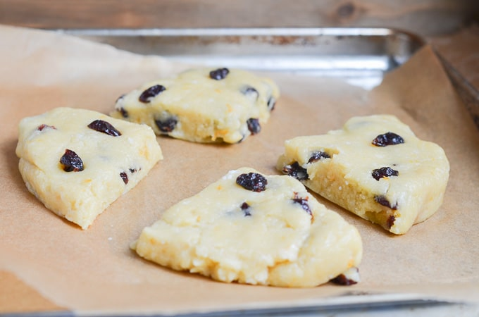 Paleo scones dough cut into four pieces on baking sheet pan.