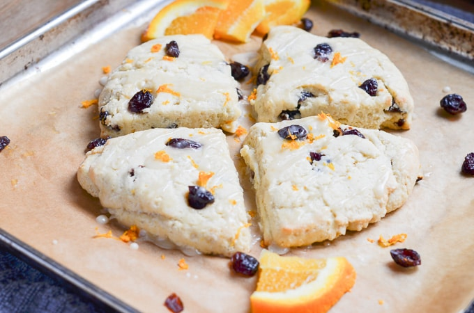 Paleo scones with icing on baking sheet.