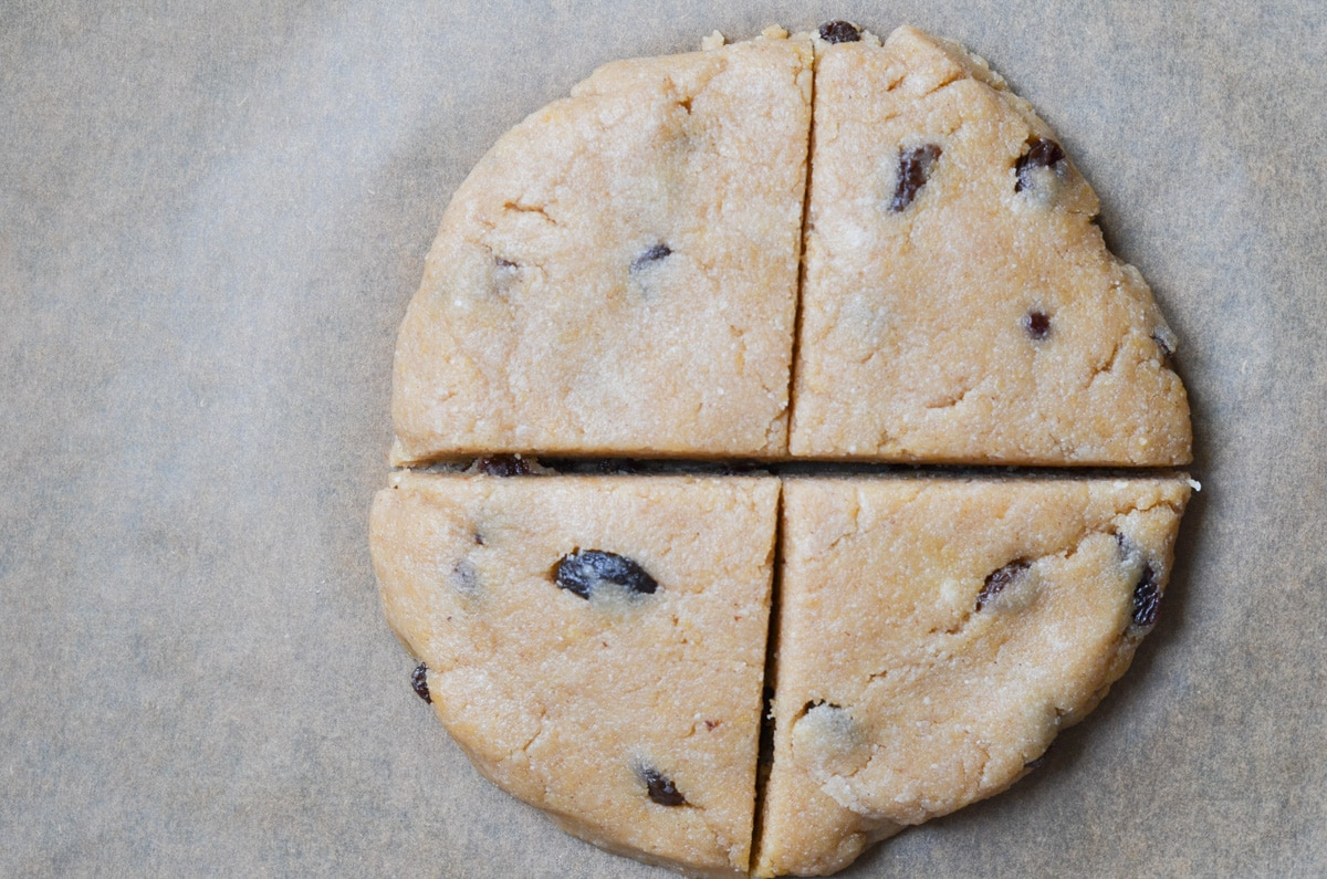 Gluten-free cinnamon raisin scone dough shaped into a round cut into four slices.