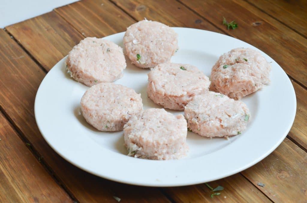 round raw sausage patties on plate.