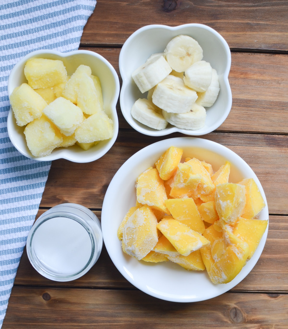 ingredients for mango smoothie bowl in small bowls on counter.