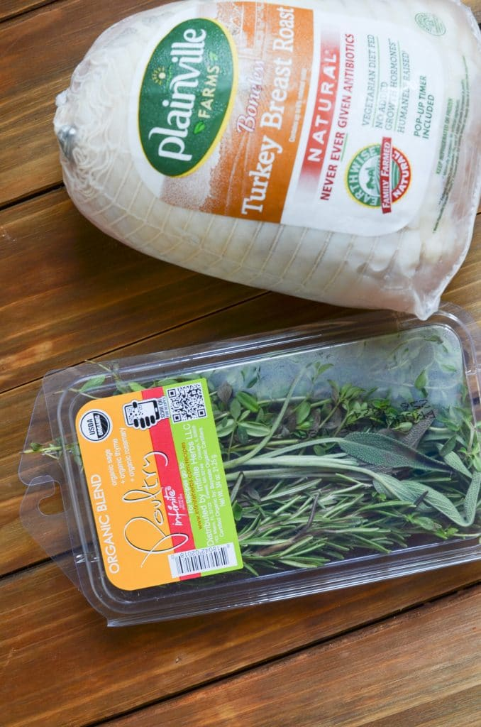 boneless turkey breast in plastic wrapping and fresh herbs.