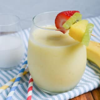 pina colada smoothie in a glass with garnishes.