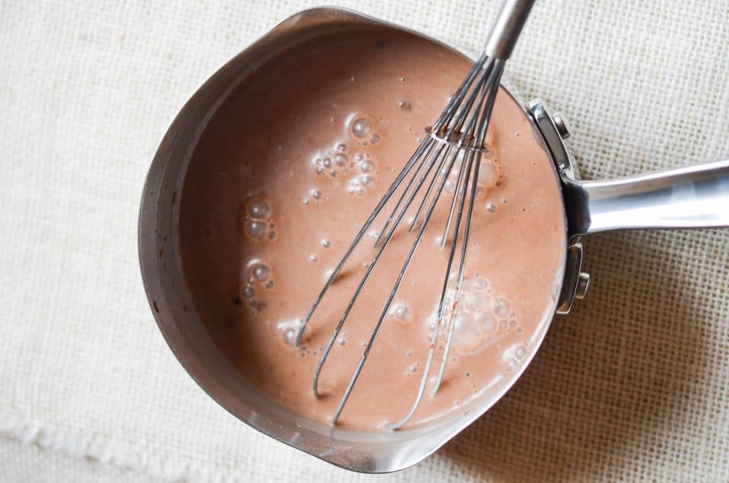 Dairy-Free Hot Chocolate in pan with whisk - 24 Carrot Kitchen