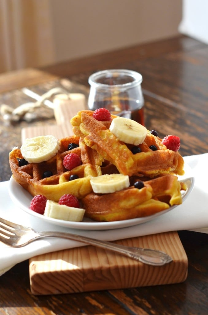 Eggless Waffles on a plate with berries and pure maple syrup - 24 Carrot Kitchen