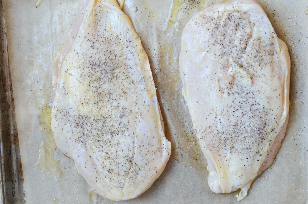 two chicken breast coated with olive oil and salt and pepper.