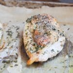 baked chicken breast on parchment lined baking pan.
