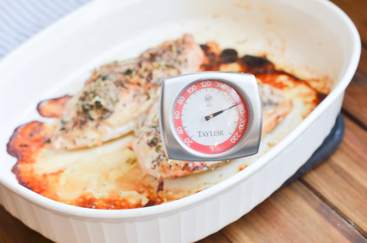 two baked chicken breasts in baking pan with meat thermometer at 170 degrees.