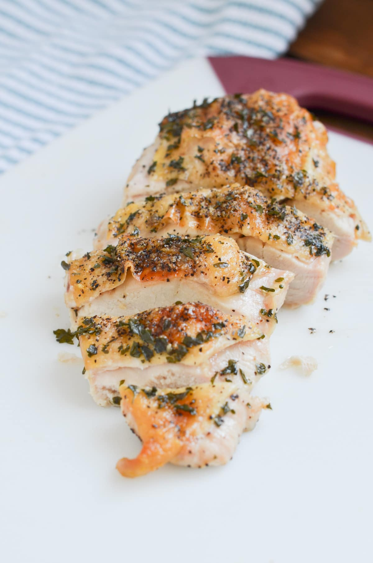 baked chicken breast sliced on cutting board.