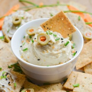 Vegan cream cheese in bowl with crackers and carrots.