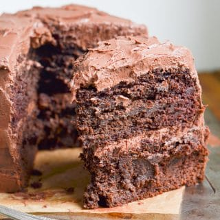Paleo Chocolate Cake double layer frosted with one slice showing.