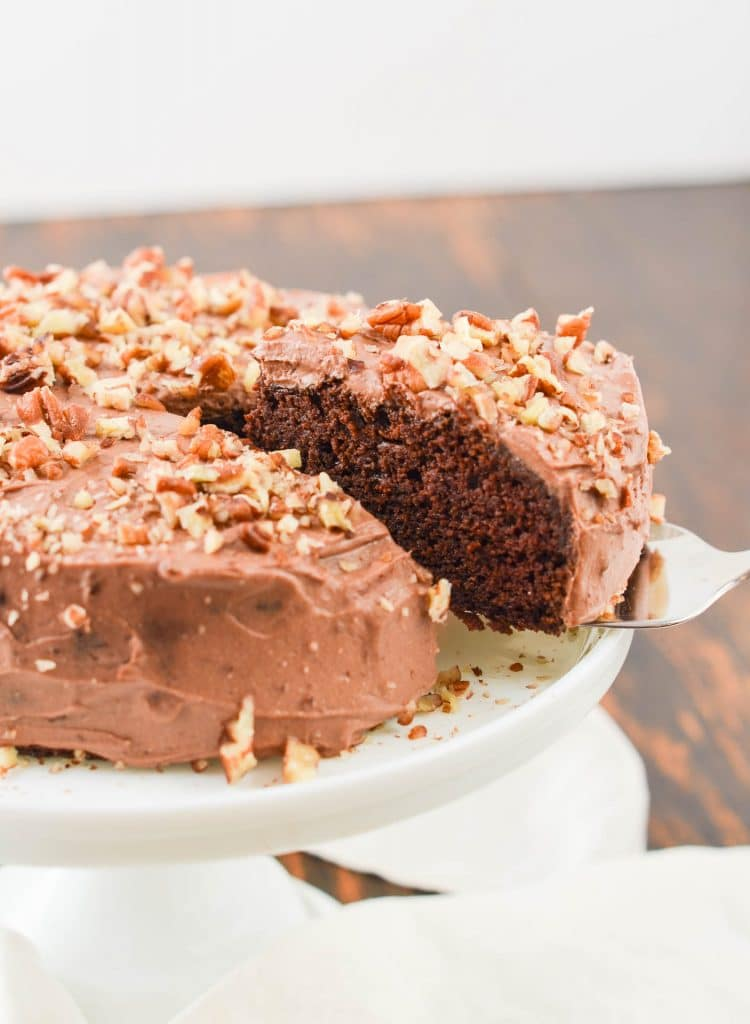 Chocolate Cake on pedestal with Chocolate Whipped Cream Frosting and chopped nuts - 24 Carrot Kitchen