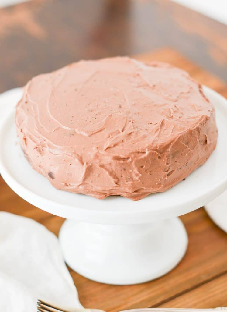 Paleo Chocolate Cake frosted with Chocolate Whipped Cream Frosting on pedestal plate. - 24 Carrot Kitchen