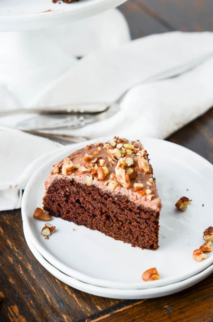 Slice of Paleo Chocolate Cake on plate with chocolate whipped cream frosting - 24 Carrot Kitchen
