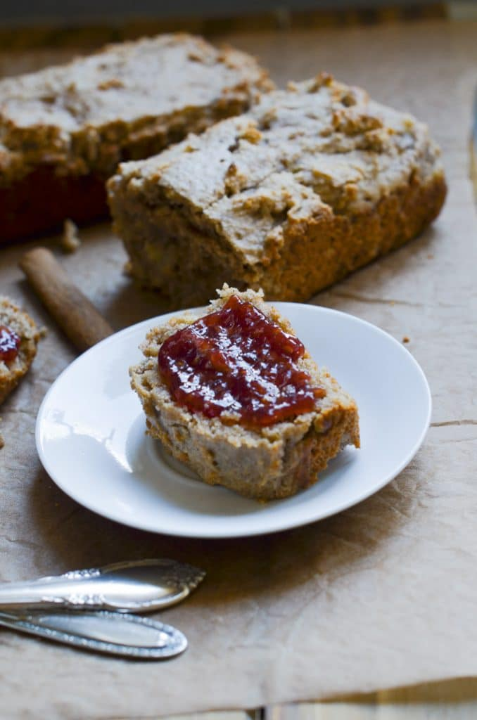 banana bread slice with jam on plate.