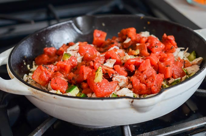 Spices, veggies, chicken and diced tomatoes in saute pan - 24 Carrot Kitchen