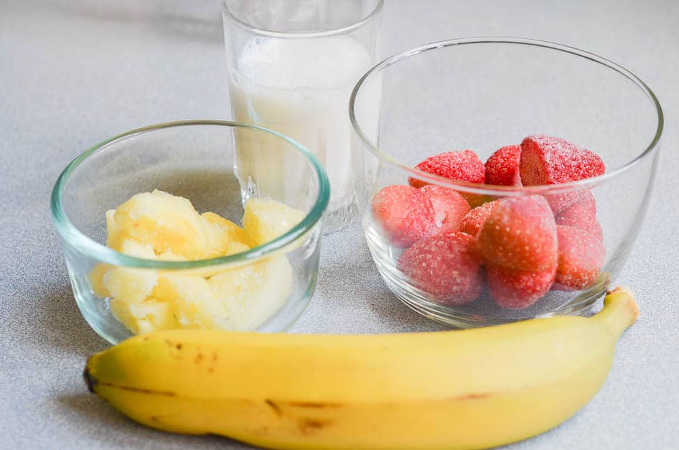 Frozen pineapple chunks in bowl, frozen strawberries in bowl, almond milk in glass, banana on table - 24 Carrot Kitchen