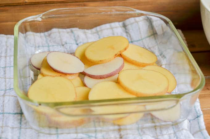 Sliced potatoes in casserole dish.