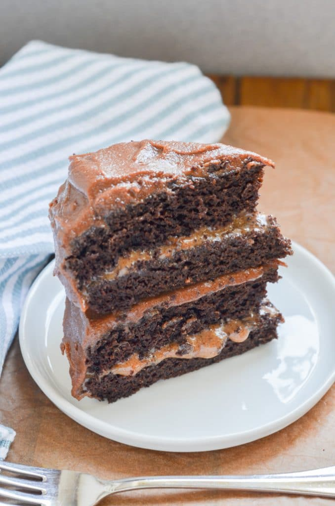 vegan caramel sauce as a layer in chocolate frosted cake slice.