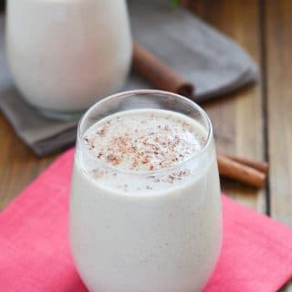 vegan eggnog in glass with sprinkle of ground nutmeg.