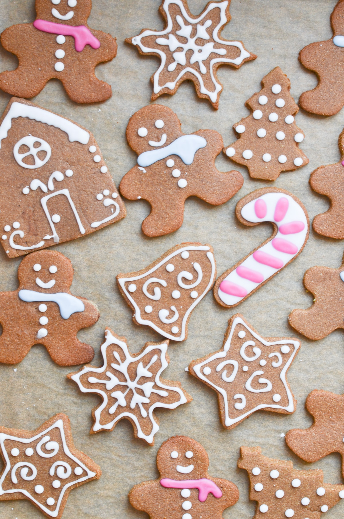 decorated gingerbread cookies on parchment lined baking sheet.
