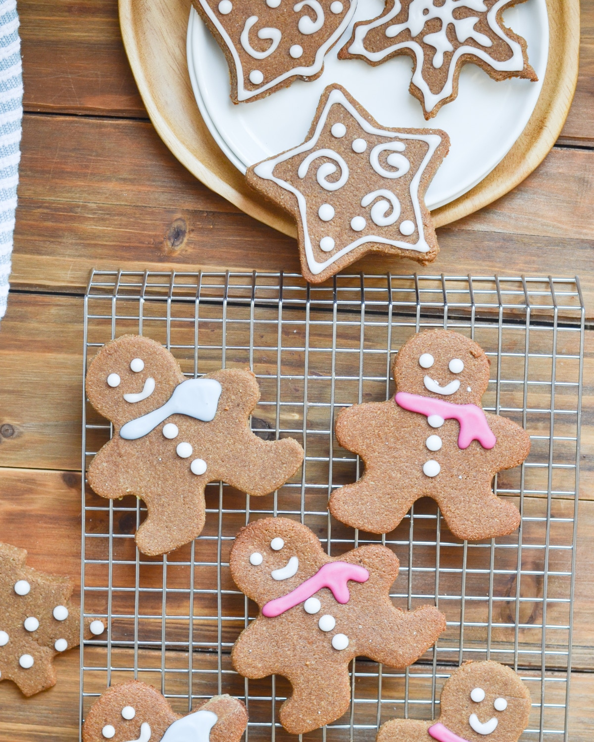 Decorated gingerbread cookies on cooling rack and plate.