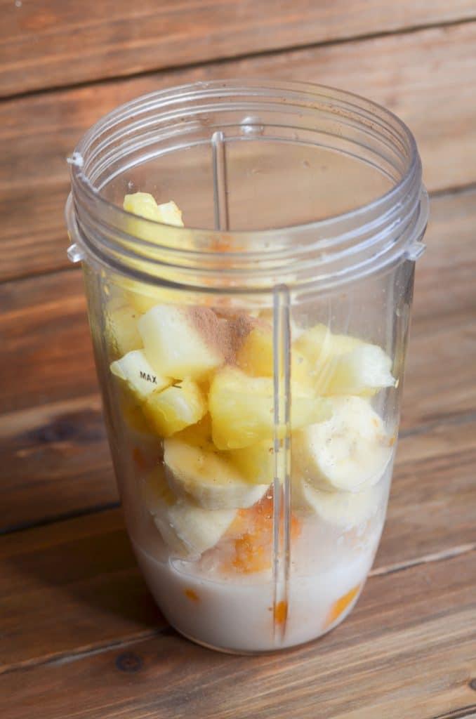 Turmeric smoothie ingredients in blender cup.