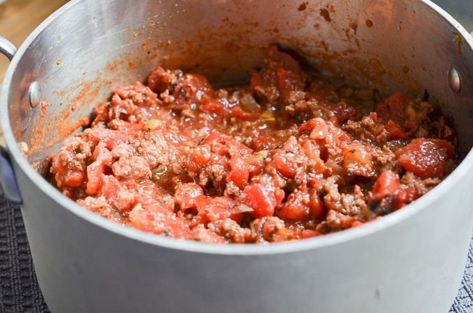 meat, tomatoes, spices in stock pot.