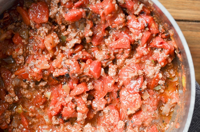 tomatoes, meat and spices in stock pot.