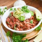 Paleo chili in a bowl with dairy-free sour cream, guacamole, wedge of lime.
