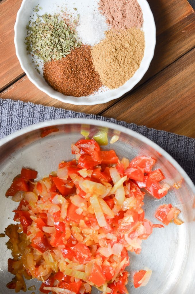 Spices in a bowl and onions, garlic and red pepper in stock pot.