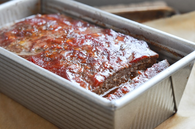 Paleo keto low carb meatloaf in loaf pan with tomato sauce.